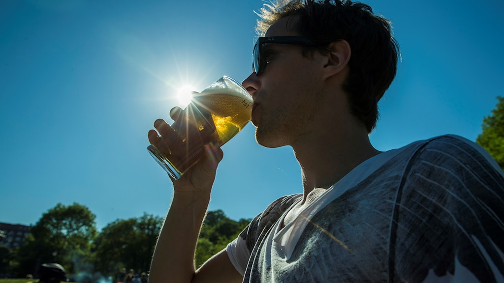 Ung man som dricker öl med solen som lyser igenom glaset.