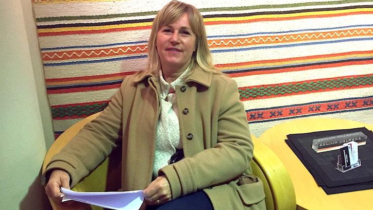 Lotta Magnusson sitter i en stol och håller i papper.
