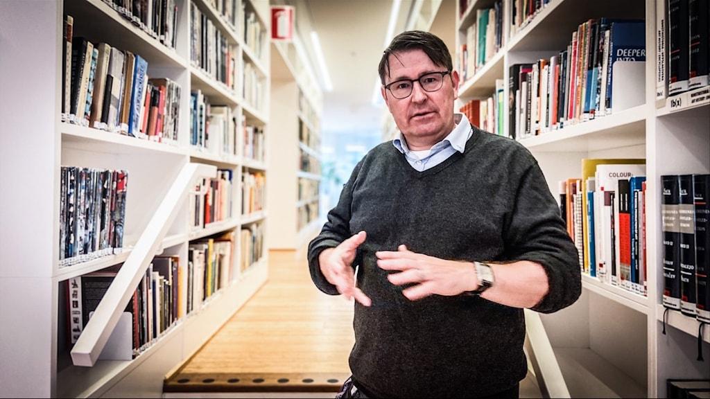 En man står och gestikulerar med händerna framför en korridor med bokhyllor på båda sidorna.