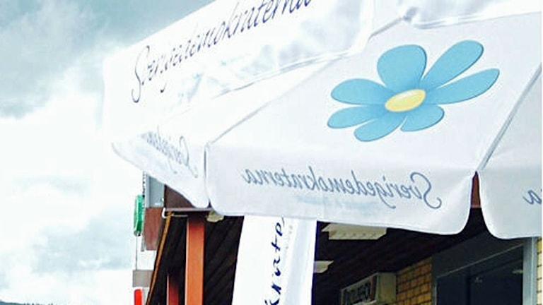 Ett parasoll med Sverigedemokraternas logga på.