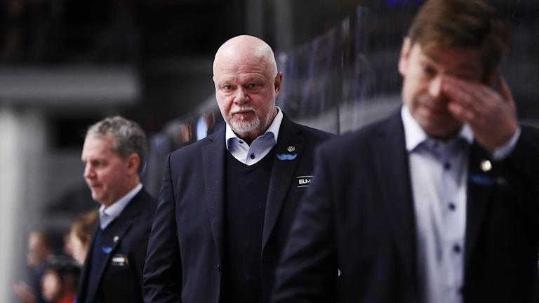 Roger Melin står i fokus mellan två andra personer, i ett bås intill en hockeyrink.