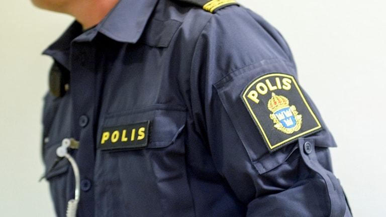 Överkropp klädd i polisuniform.