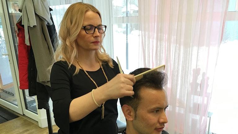 En frisör kammar Zabi Khaliqi hår.