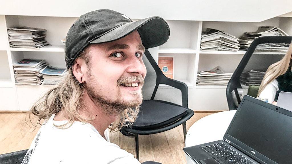 Ung man med keps framför en bärbar dator.