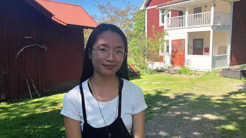En ung kvinna med glasögon i sommarmiljö