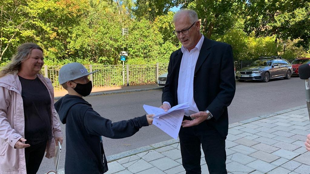 Wiktor Johansen och Bodil Andersols från Linghed lämnar över namninsamlingen till kommunfullmäktiges ordförande Göran Forsen (M).