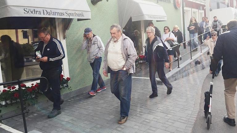 Flera personer står i kö utanför en bank.