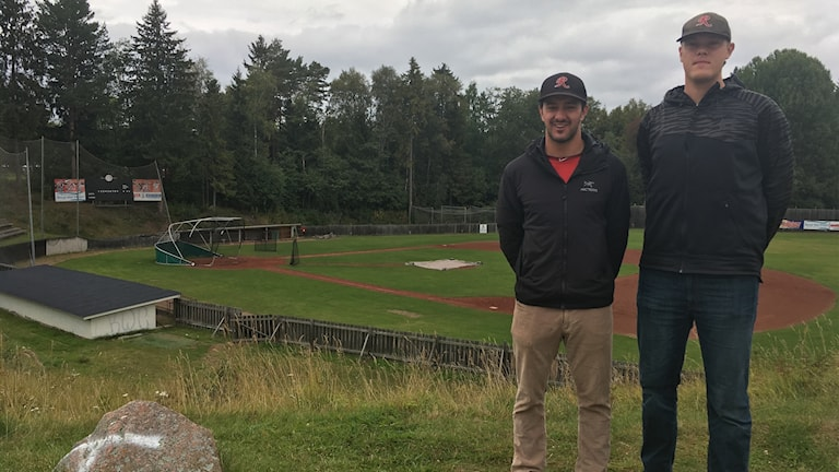 Jakob Syrén, pitcher, och Ketch Marsh, coach, i baseballlaget Rättvik Butchers framför baseballplanen i Rättvik.