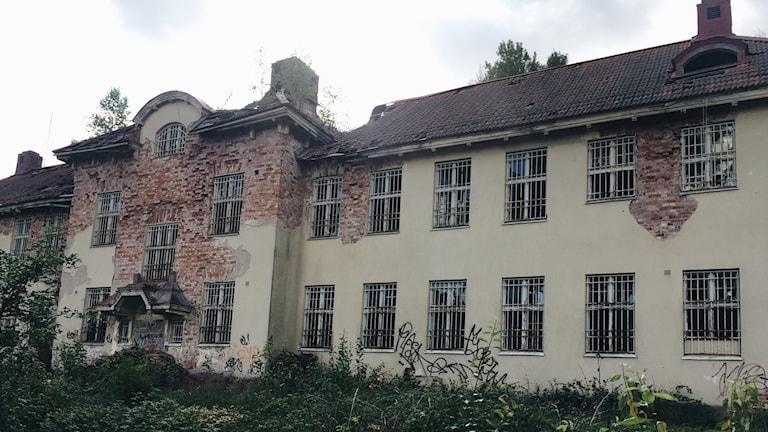 En sliten byggnad där fasaden flagnat och teglet blottas.