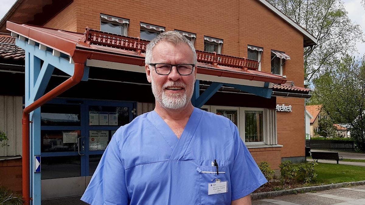 Distriktsläkare Gunnar Svärd står framför sin arbetsplats Kvarnsvedens vårdcentral i Borlänge. Han bär en ljusblå skjorta och står och tittar in i kameran. Bakom honom ett rött tegelhus och det är sommar på bilden.