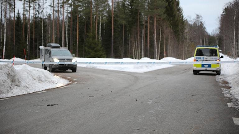 En mörk bil och en polisbil bakom polisavspärrningsband i en grusvägskorsning vid en skog.