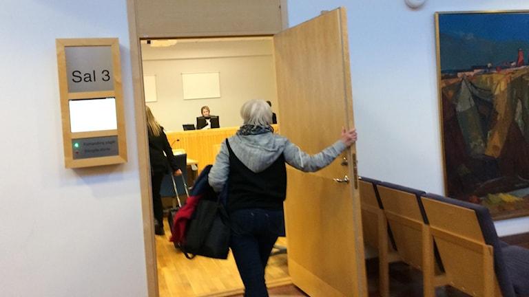 En person går in salen där rättegången hålls idag