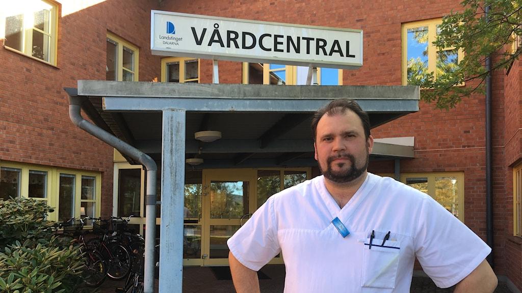 Allmänläkaren Henrik Backolars står framför ingången till vårdcentralen i Gagnef.