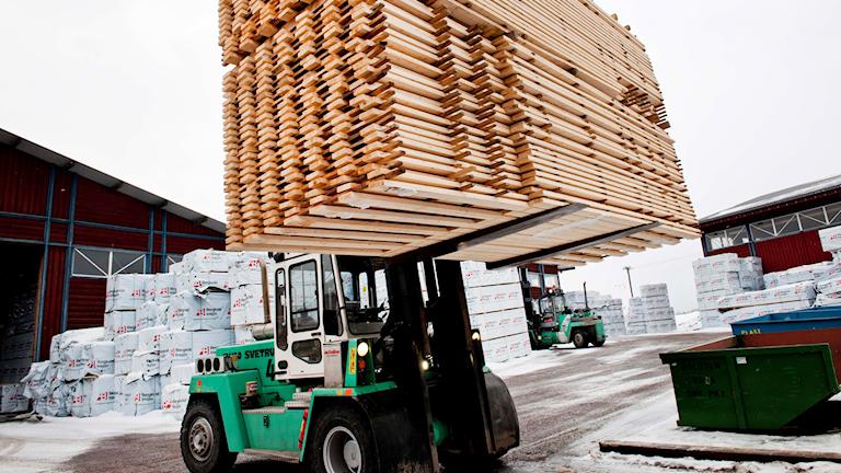 Maskin lyfter och transporterar plankor på sågverket Bergkvist-Insjön.