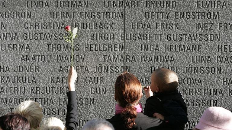 Anhöriga håller upp en ros framför Estoniamonumentet, där omkomnas namn är inristade i sten.