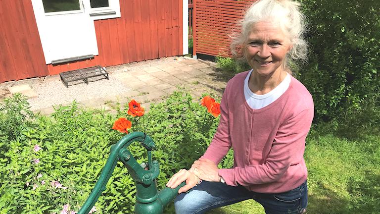 Annichen Kringstad på knä vid en vattenpump i en grönskande trädgård.