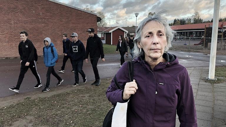 Skolsköterskan Marianne Börjesson på skolgården och där elever passerar i bakgrunden.