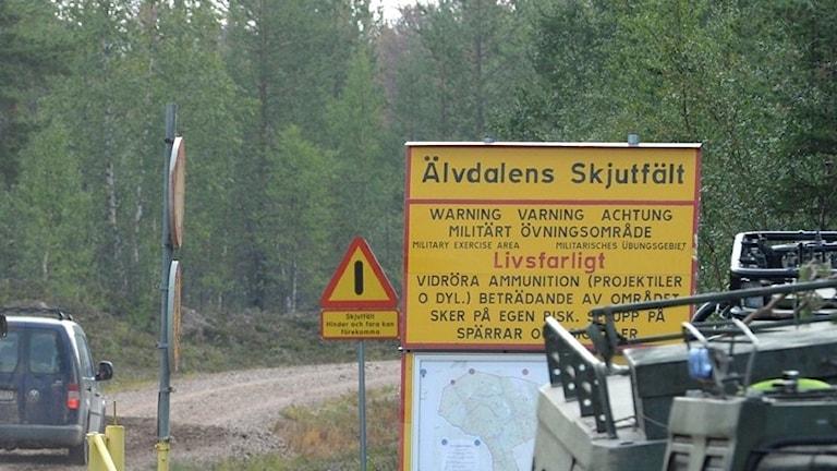 Ingång till Älvdalens skjutfält. Militära fordon och några människor på vägen.