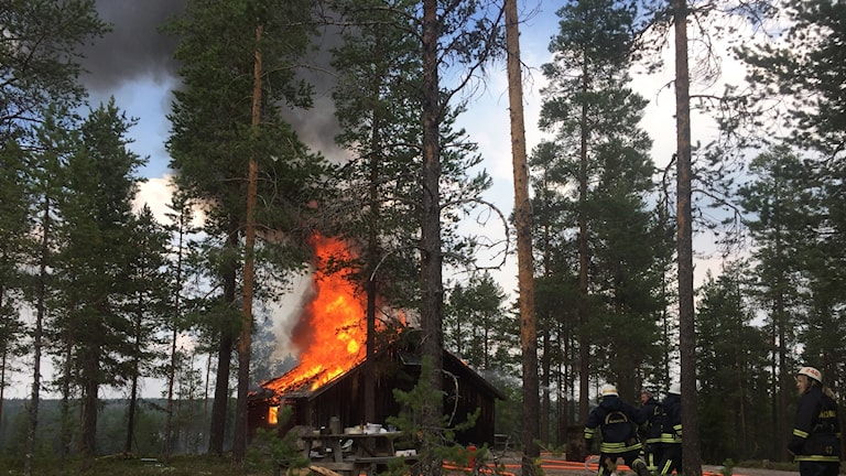 Byggnad brinner i skogen.