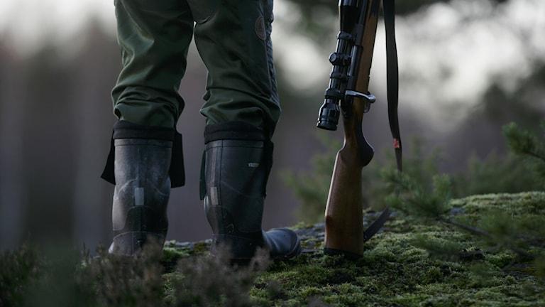 Två ben i stövlar står i mossan med ett gevär lutat mot marken bredvid sig.