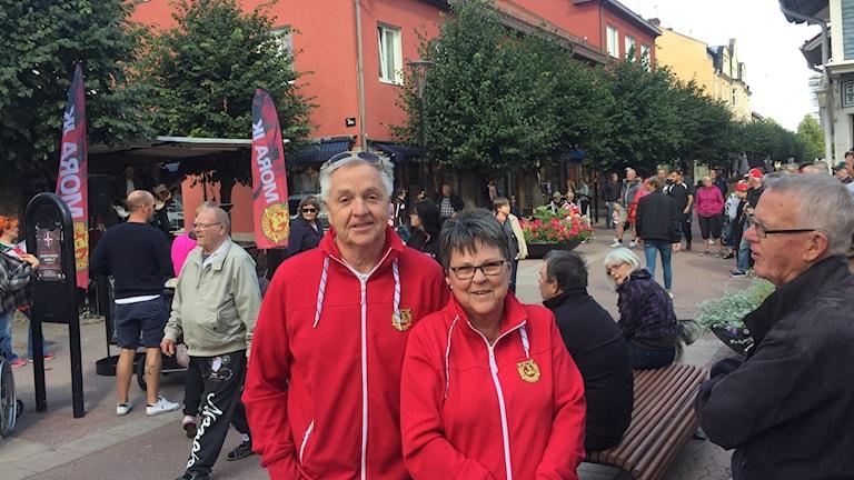 En man och en kvinna i röda tröjor på en gågata.