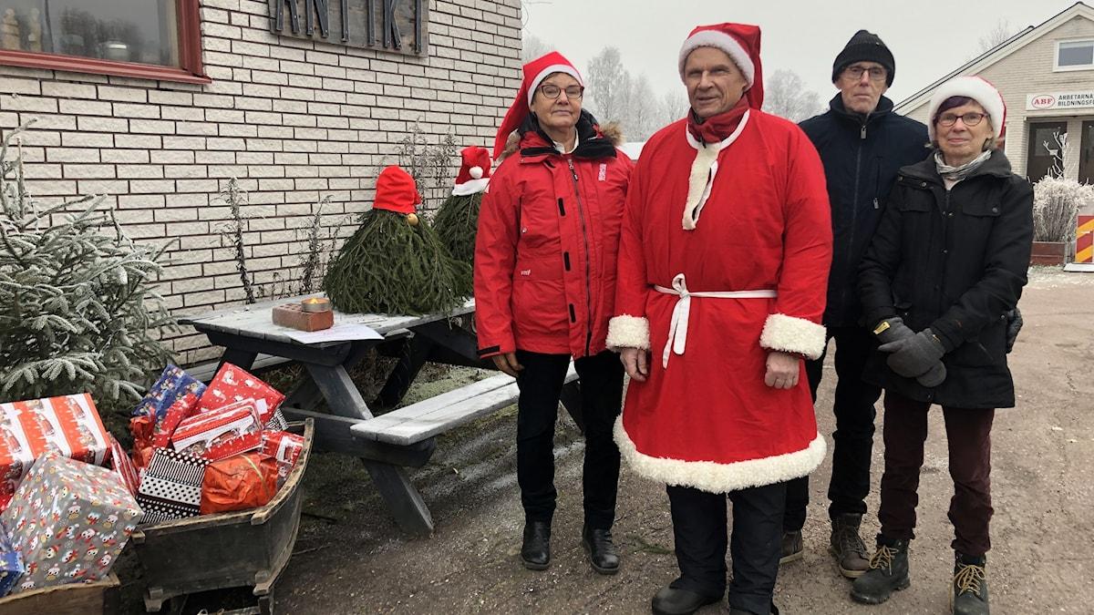 En man och en kvinna i rödvita jackor och tomteluvor samt en man och en kvinna i svarta kläder står utomhus vid ett julpyntat bord med inslagna julklappar.
