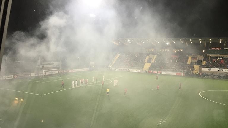 Fotbollsplan med vit rök.