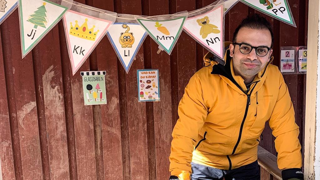 Utländsk man med orange jacka som står på en förskolegård i uppbyggd glasskiosk. I förgrunden vimplar med alfabetets bokstäver och färgglada bilder.