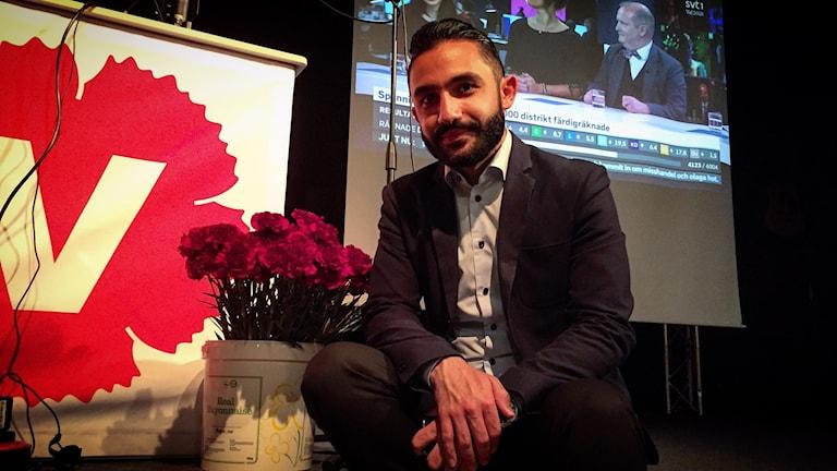 Daniel Riazat sitter framför talarstolen på Vänsterpartiets valvaka i Falun med en bukett röda nejlikor bredvid sig.