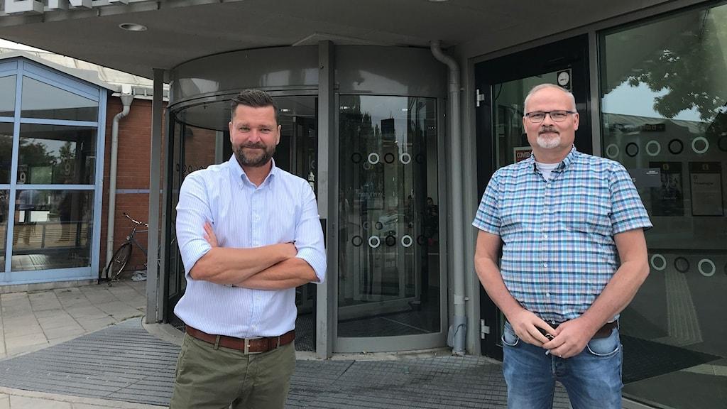 Två män framför en svängdörr