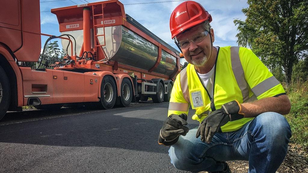 En man i röd hjälm och varselväst sitter på knä på en asfalterad väg. I bakgrunden syns en stor orange lastbil.