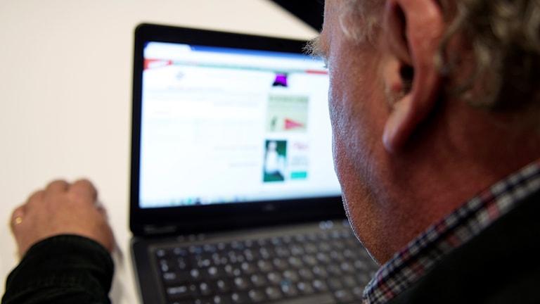 En man vid en dator, man ser inte ansiktet och skärmen är suddig.