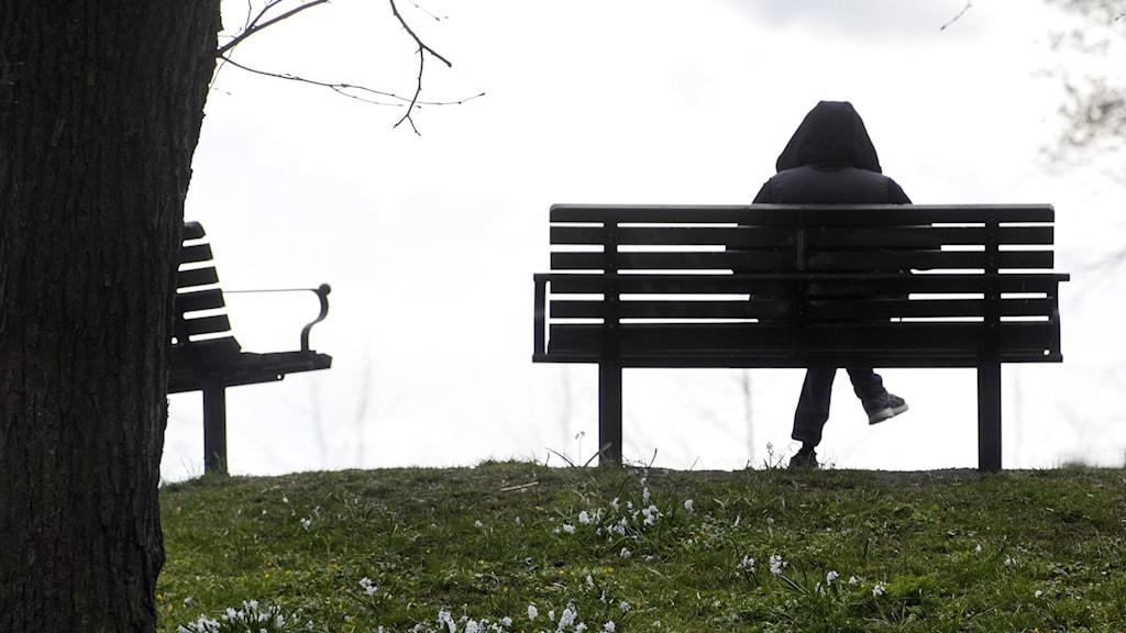 En anonym kvinna som sitter på en bänk.