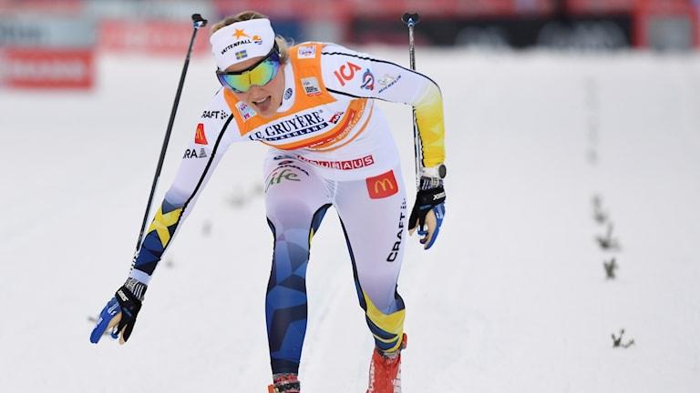 Stina Nilsson när hon går i mål i 10 kilometer klassiskt i Finska Ruka.