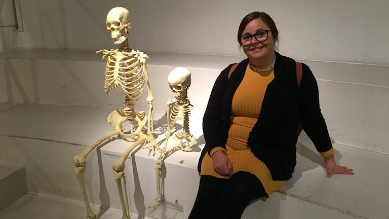 Anna Tornberg, forskare, sitter bredvid två skelett.