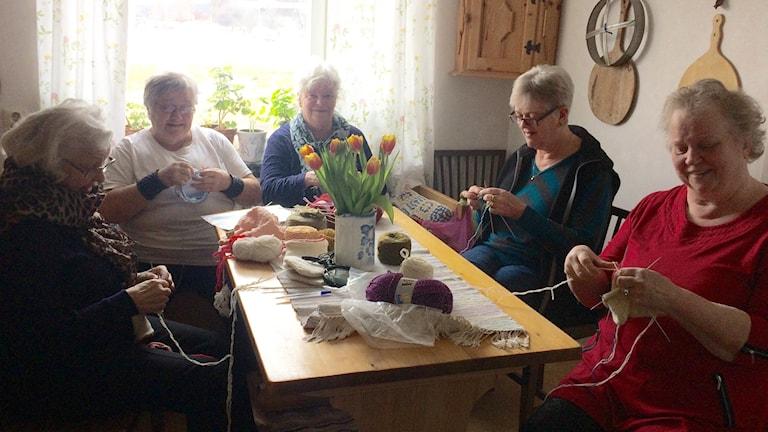 Fem kvinnor sitter runt ett bord och stickar.