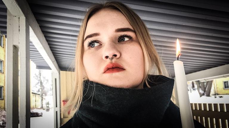En tjej står under ett tak med ett ljus i handen.