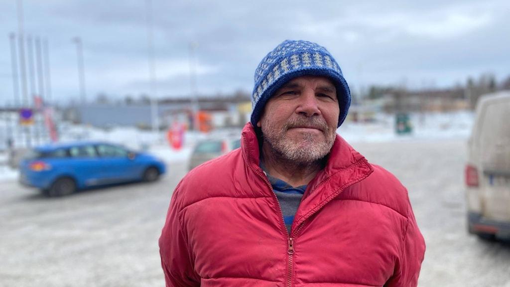 En man i röd jacka och blå mössa