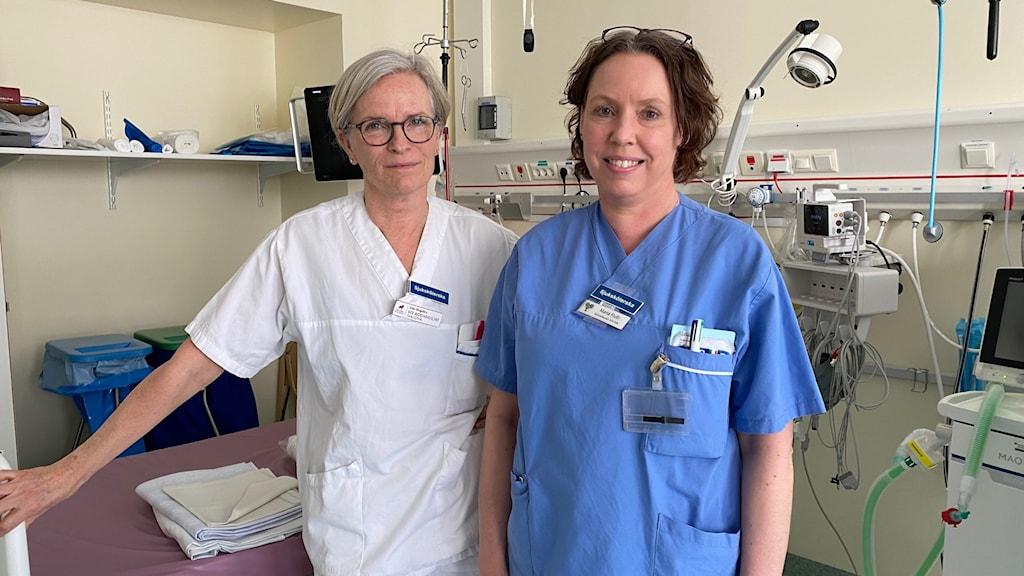 En kvinna i vita vårdpersonalkläder och en kvinna i blå vårdpersonalskläder.