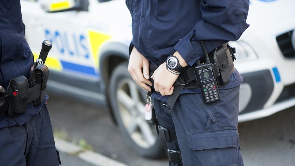 Delar av två polisklädda personer med en polisbil i bakgrunden.
