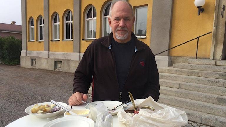 Lars Herre framför en surströmmingsbuffé