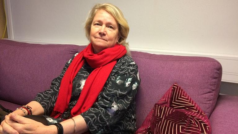 Anna-Lena Söderlund Törnell sitter i en soffa med händerna knäppta kring knät.