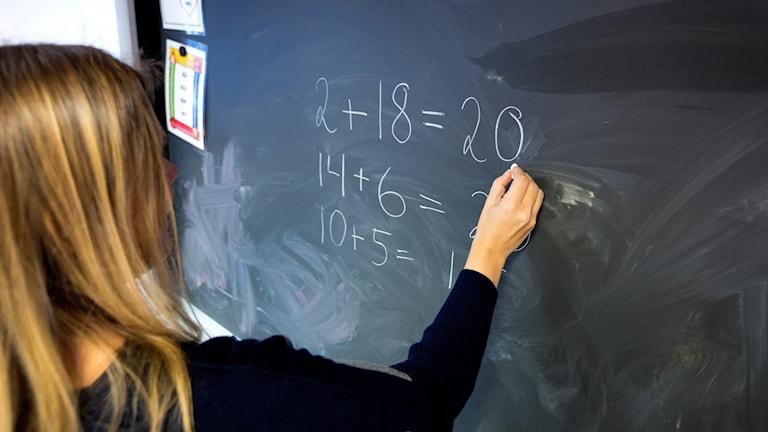 Lärare med långt hår skriver siffror på svarta tavlan