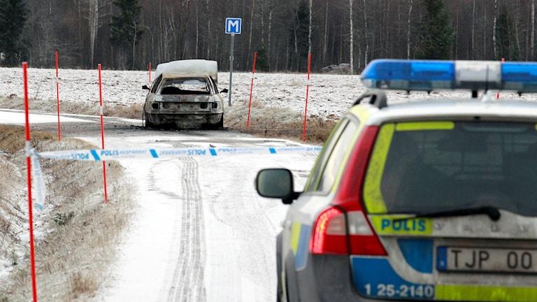 Polisbil, avspärrningsband, utbrunnen bil.