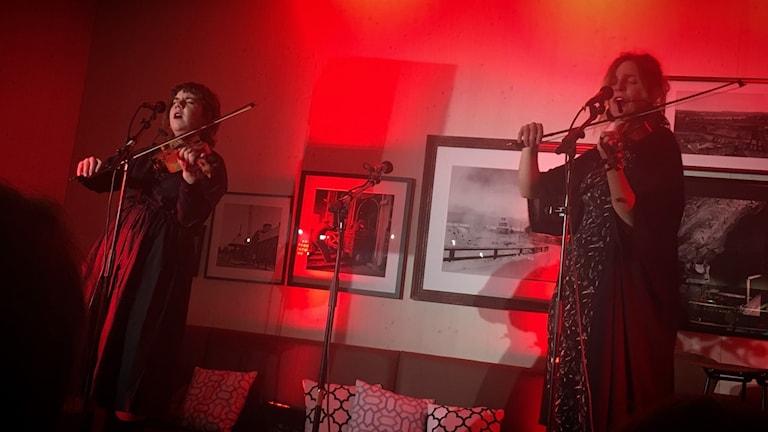 Två kvinnor sjunger och spelar fiol på en scen.
