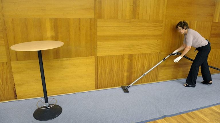 En kvinna dammsuger en heltäckningsmatta i en konferenssal.