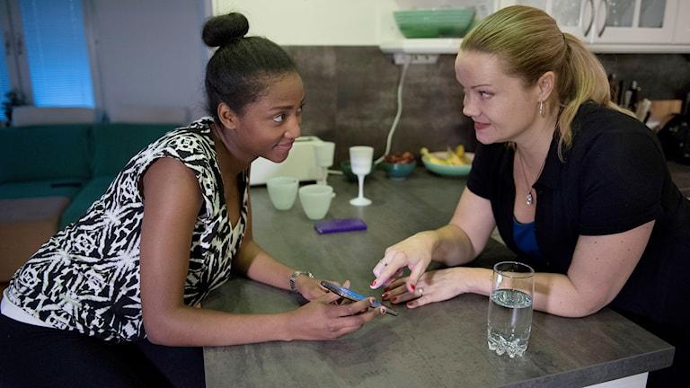En flicka och en kvinna sitter och pratar och visar något på en mobiltelefon.