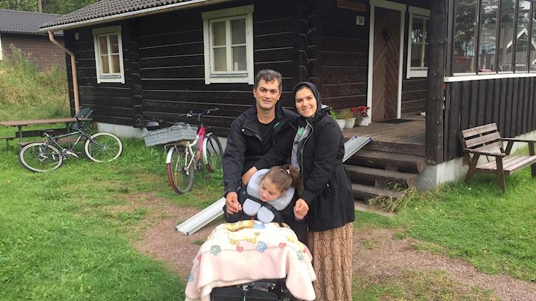 Karim och Razie tillsammans med sin dotter utanför sin stuga.