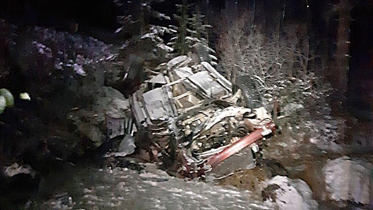 Skadad bil efter trafikolycka, skrotdelar ligger i buske och dike
