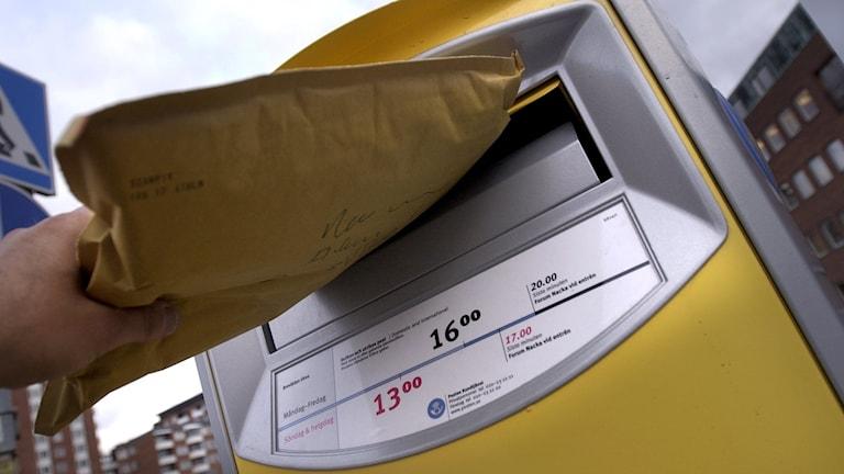 Någon postar ett paket/brev i en gul postlåda.
